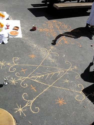 Veve drawings in Cornmeal on pavement.