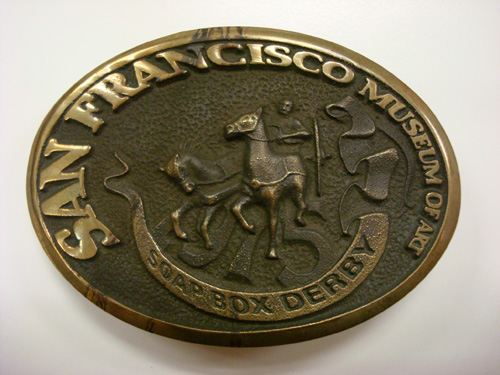 SFMA Artist's Soap Box Derby, Commemorative Belt Buckle, 1975; brass; designed by Don Rich