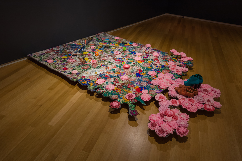 Ebony G. Patterson, Where We Found Them, 2014; mixed media jacquard weaved tapestry with jewelry, shoes, gold chains, tassels, 100 crochet flowers, 8ft x 6ft; installation view of Dead Treez, installation view, John Michael Kohler Arts Center in Sheboygan, Wisconsin; courtesy Monique Meloche Gallery